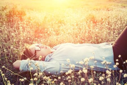 Happy hipster woman lying down on dandelion field close her eyes feeling comfortable