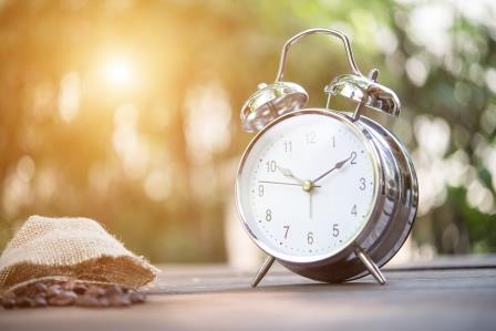 Retro alarm clock on wooden table. Nature background.