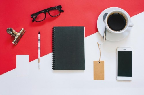 Creative flat lay photo of workspace desk with smartphone, eyeglasses, coffee, tag and notebook with copy space background